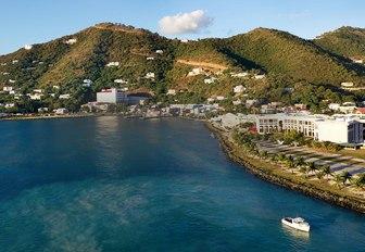 A single yacht cruising close to the coast of a British Virgin Island