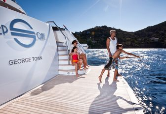 a family try out fishing on the swim platform of charter yacht 'Step One'