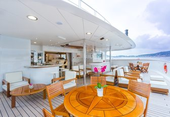 outdoor area with tables and lounging options on board charter yacht LEGEND