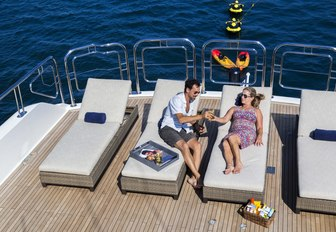 charter guests relax on sunbeds on the sundeck of luxury yacht Far From It