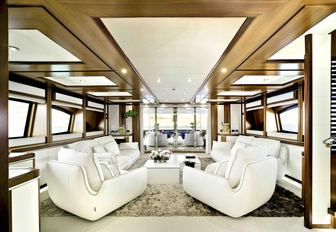 luxury yacht bunker main salon with white sofas and view of exterior dining