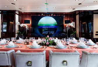 Formal dining salon on luxury charter yacht HEMILEA, with peach tablecloth and green and blue artwork in centre of wall
