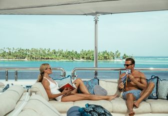 charter guests relax in the seating area on the sundeck of superyacht CALYPSO