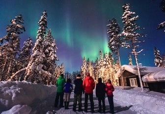 people stand below northern lights in norway