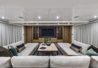 U-shaped sofa faces large TV on board charter yacht Liquid Sky