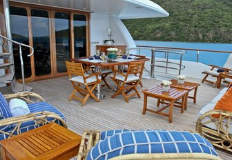 table, chairs and lounging areas on the upper deck aft of charter yacht M4