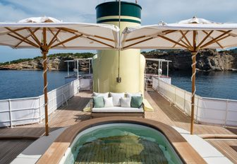 Spa pool on top deck of classic yacht, with twin parasols either side