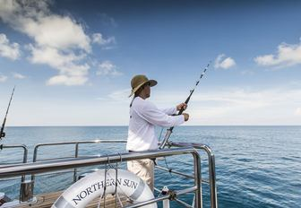 charter guest fishes from swim platform of superyacht 'Northern Sun'