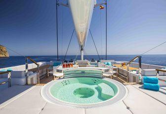 Jacuzzi surrounded by sunpads on the sundeck of luxury yacht AQUIJO