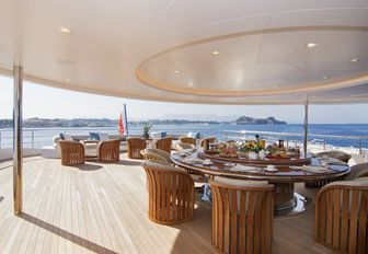 circular dining table on the shaded section of the upper deck aft aboard luxury yacht O'PTASIA
