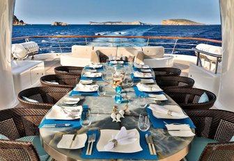 al fresco dining setup on the sundeck of charter yacht DENIKI