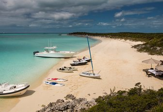 beach in the bahamas with yacht toy selection laid out on sand