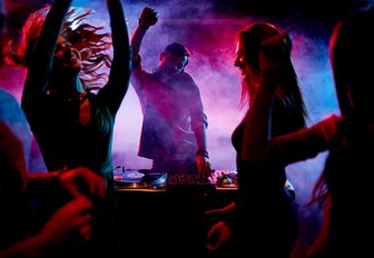 Young people party around DJ set-up with smoke and red and blue lights