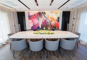 formal dining area looked over by contemporary artwork aboard superyacht OURANOS