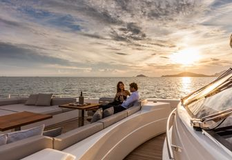 guests enjoy a glass of wine on the foredeck of luxury yacht December Six as the sun sets
