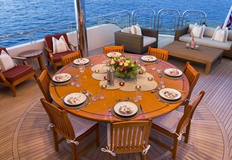 circular dining table on the upper deck aft of charter yacht Far From It