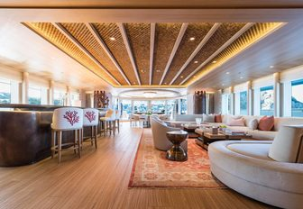 inviting salon with sumptuous seating and a bar on board charter yacht Here Comes The Sun