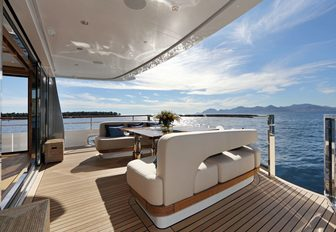 table and chairs on aft deck of superyacht SOLIS with stairs leading to swim platform