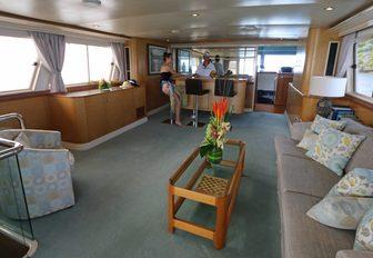comfortable lounge and bar in main salon of charter yacht BAHAMA