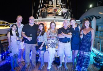 attendees pose on the deck of a yacht at night at the Thailand Yacht Show & Rendezvous
