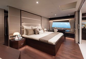 the spacious master cabin inside charter yacht impatient IV with a grand window that opens up to the Mediterranean
