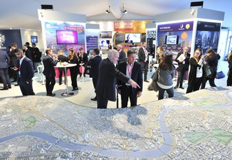 exhibitioners talk to attendees during MIPIM, held annually in Cannes