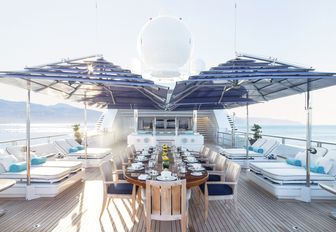 alfresco dining table with sun-loungers either side on the upper deck aft of charter yacht TITANIA