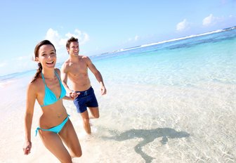 a couple who are on a luxury yacht vacation to the bahamas are running on a beach