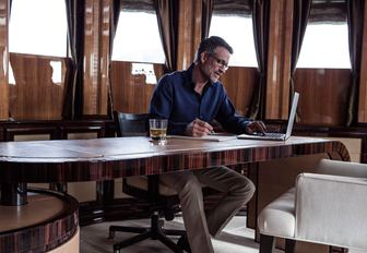 charter guest catches up on business in private master suite office aboard superyacht MEAMINA