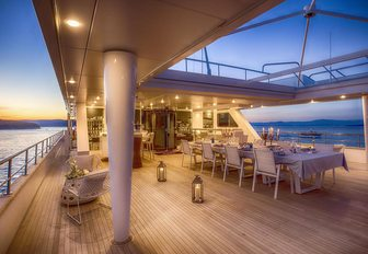 spacious alfresco dining area at sunset on board luxury yacht KATINA