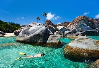 snorkeller explores boulder-strewn the baths in Virgin Gorda in the Virgin Islands