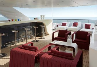 The sophisticated sun deck of charter yacht HOME with cocktail bar and lounging seats overlooking the ocean f