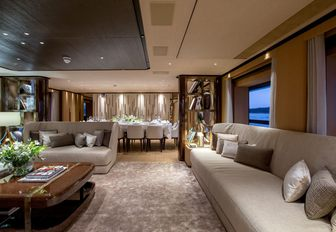 sofas and dining table beyond in the main salon aboard charter yacht VERTIGE