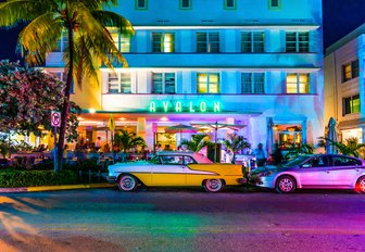 vintage cars park outside Art Deco hotel along South Beach at night