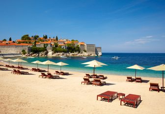 canvas chairs and loungers line up on white sand beach in Montenegro
