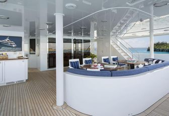 aft deck seating area with navy blue upholstery on board charter yacht Time For Us