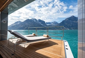 Sun loungers looking out across the water from a retractable balcony on board superyacht CLOUDBREAK