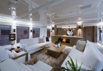 salon with white sofas and fireplace on board luxury yacht Liquid Sky