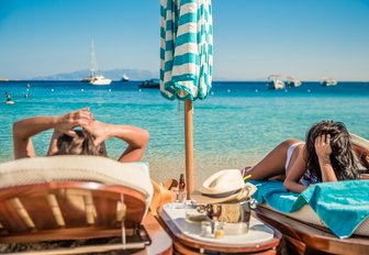 two females relax on sun loungers at Nammos beach club, Mykonos, Greece