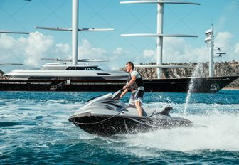 jet-ski riding alongside yacht