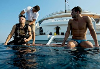 Two men sat on edge of O'MEGA superyacht with legs in water