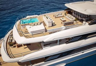 large pool, seating and shaded dining area on the sundeck of luxury yacht Spectre