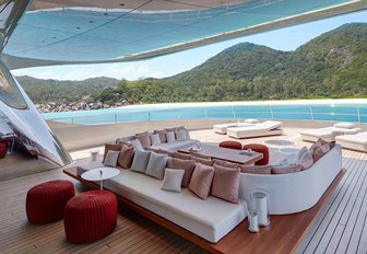 looking out of superyacht Savannah spacious sun pads to a tropical mountainous island
