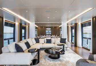 seating area flanked by full-length windows in the main salon aboard motor yacht Vista Blue