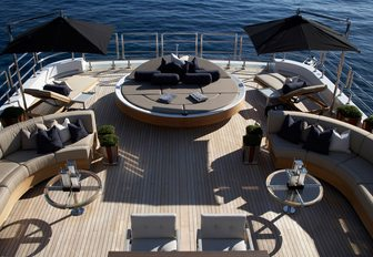 The spacious aft sundeck of charter yacht SEALYON with luxurious and curvaceous sunpads and loungers