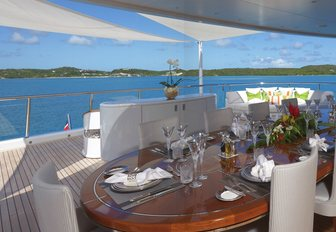 oval table is set for a lunch on the bridge deck aft of luxury yacht AMARYLLIS