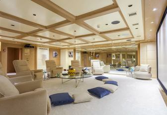 Soft seating area on O'MEGA superyacht with large screen in background