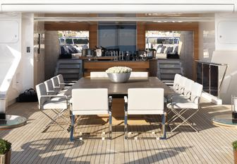 the alfresco dining table and cocktail bar partitioning the fore and aft sundeck of motor yacht SEALYON