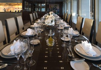 Formal dining arrangement onboard SERENITY, long dining table with elegant decor, with white upholstered chairs along either side