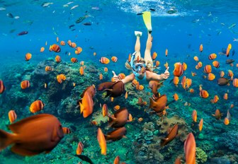a luxury yacht charter guest scuba diving during her vacation in the bahamas